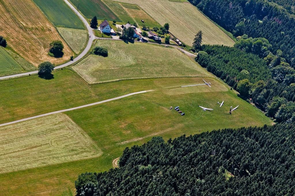 """Die Flugzeuge stehen hier bei Ostwind auf dem höher gelegenen Plateau des Westendes. Die Landungen erfolgen bei Ostwind in der Regel mit Rückenwind den Berg rauf. Beim Zurückholen der Flugzeuge aus dem """"Ostwindlandefeld"""" (hier links im Bild teilweise als helle gemähte Fläche zu sehen) haben wir motorisierte Helfer (siehe nächstes Bild)."""